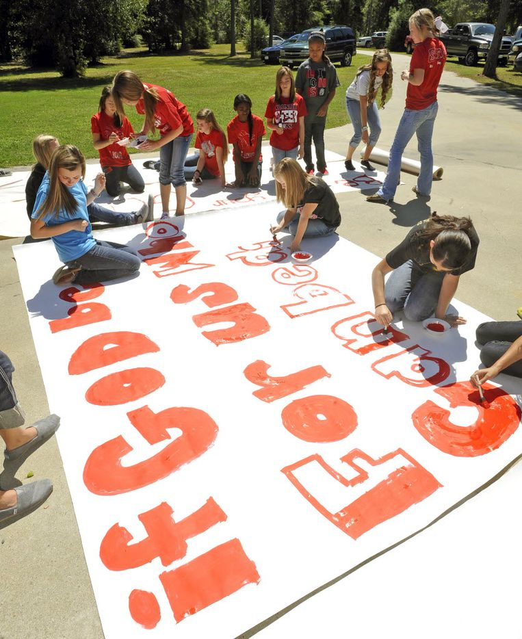 In this 2012 file photo, Kountze High School cheerleaders and other children work on a large sign.