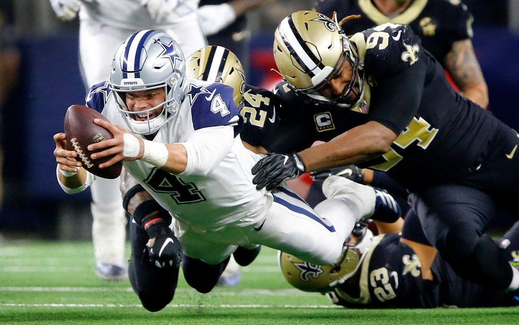 Dallas Cowboys quarterback Dak Prescott (4) dives for extra yards and a first down as he's brought down from behind by New Orleans Saints strong safety Vonn Bell (24) and defensive end Cameron Jordan (94) during the fourth quarter at AT&T Stadium in Arlington, Texas, Thursday, November 29, 2018. The Cowboys pulled out a 13-10 win.