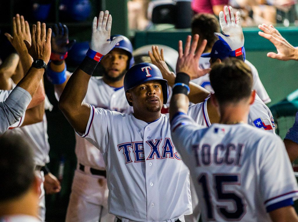 Texas Rangers designated hitter Adrian Beltre (29) and shortstop Elvis Andrus (1) get high fives in the dugout after scoring two runs thanks to a hit by third baseman Jurickson Profar (19)  during the fifth inning of an MLB game between the Texas Rangers and the Oakland Athletics on Thursday, July 26, 2018 at Globe Life Park in Arlington, Texas. (Ashley Landis/The Dallas Morning News)