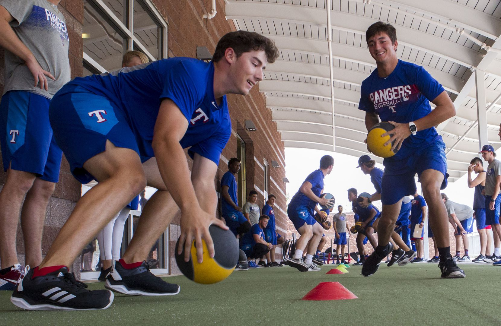Texas Rangers' pitcher Cole Winn (left) gets the upper hand on Owen White(right) while working on drills that improves strength, agility and quickness at the Rangers' training facility Friday, Aug. 10, 2018 in Surprise, Arizona.