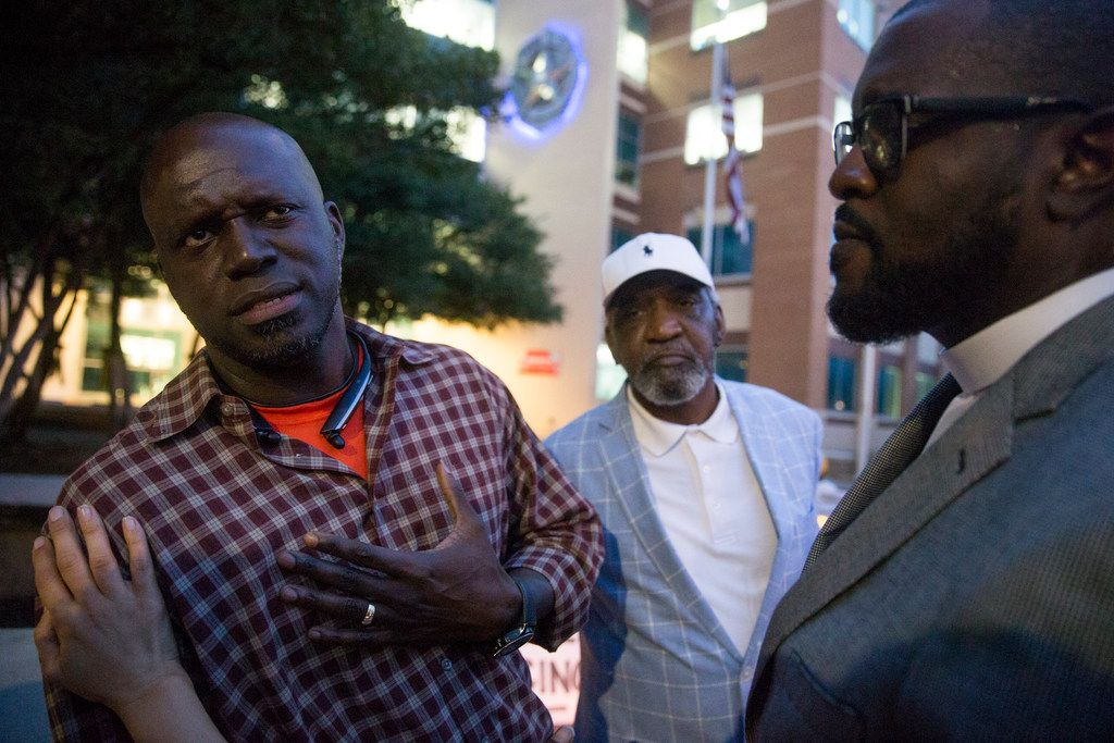 Jean family friend Dane Felicien (left) talks to pastors Robert Conley and Michael W. Waters (right) before speaking at a Mothers Against Police Brutality candlelight vigil for Botham Jean a day after he was killed in his own apartment.