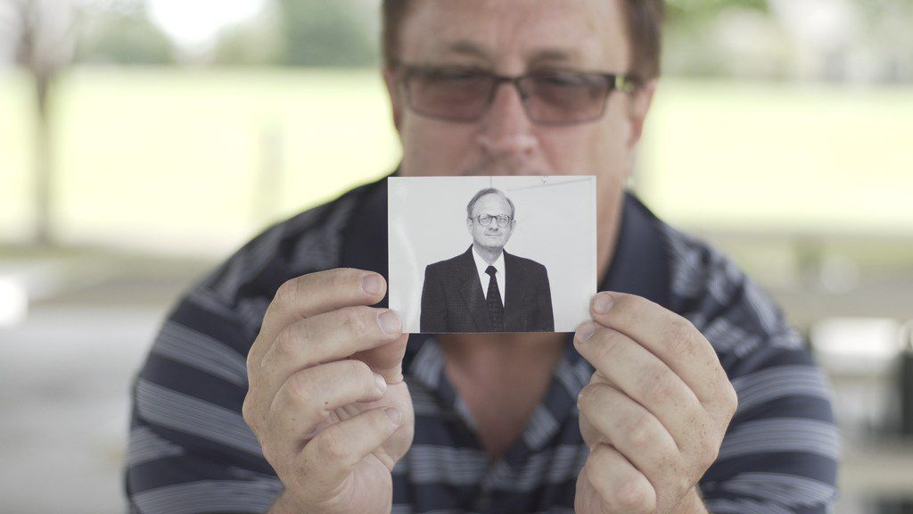 Guy Moore, son of the Rev. Charles Moore, holds a photo of his father in the PBS Independent Lens documentary Man on Fire. about his father's death