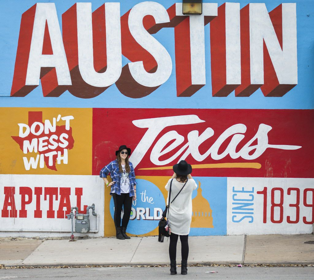 SXSW attendees take photos next to a mural on Sixth Street.