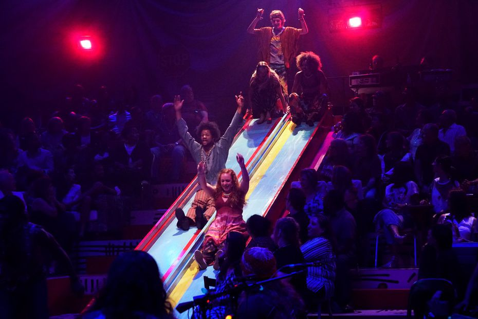 The cast of Dallas Theater Center's  Hair  come down the slide at the Wyly Theatre.