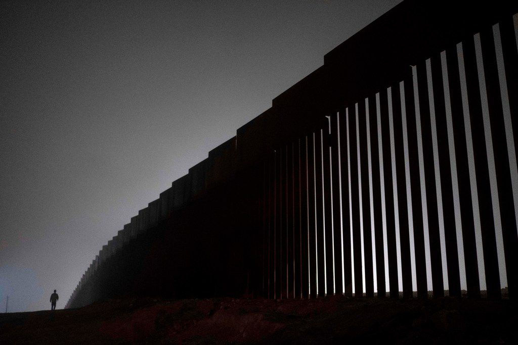 A man walks next to a reinforced section of the US-Mexico border fence is seen from Tijuana, Baja California state, Mexico on December 20, 2018.