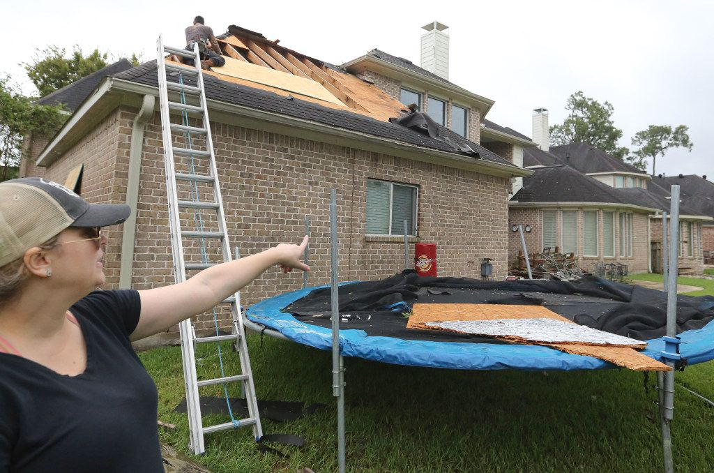 Christy Petrie points out the damage on her house after a tornado spawned by Hurricane Harvey hit the Sienna Plantation subdivision southeast of Houston on Saturday, August 26, 2017. (Louis DeLuca/The Dallas Morning News)