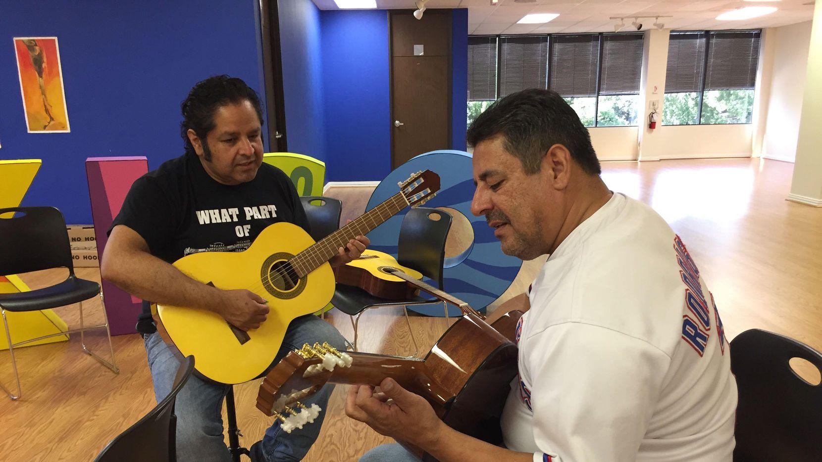 Antonio Salas  (izq.) enseña guitarra a Raul Saldaña, el sábado 8 de junio en el consulado mexicano en Dallas. (AL DÍA/CARMINA TISCAREÑO)