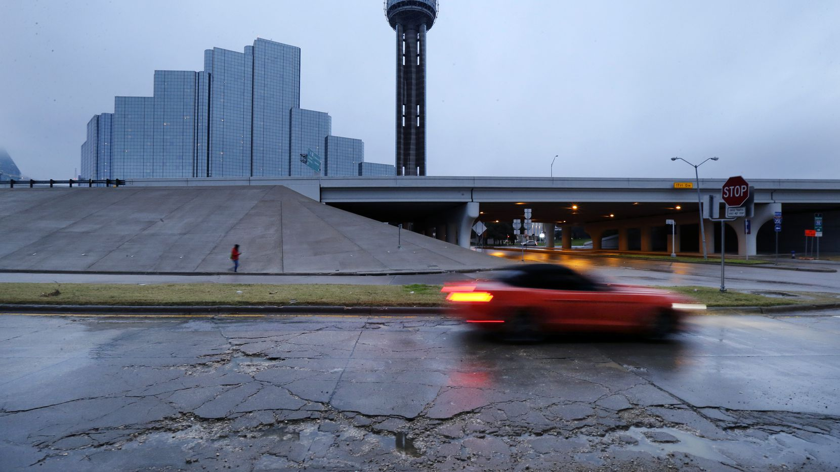 A car pass through broken up concrete and rain-water filled potholes near Reunion Tower in downtown Dallas, Wednesday, Jan. 2, 2019.