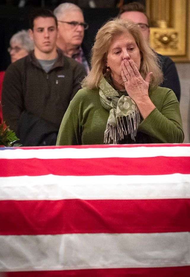 Amy Estabrook, a first cousin, once removed, of the former President, blows a kiss toward the flag-draped casket of President George H.W. Bush as he lies in the Rotunda of the U.S. Capitol on Tuesday, Dec. 4, 2018, in Washington.