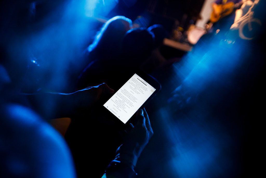 Meryl Evans pulls out her cellphone to follow along with the song lyrics during a concert by William Clark Green at Lava Cantina in The Colony. Evans is deaf and loves to go to concerts.