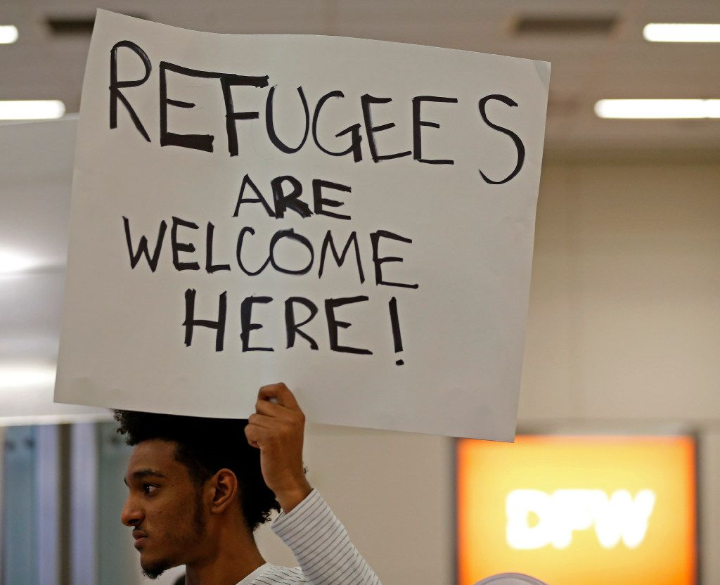 Sami Abdalla holds up a sign while he waits for his grandmother from Sudan to be released at DFW Airport.