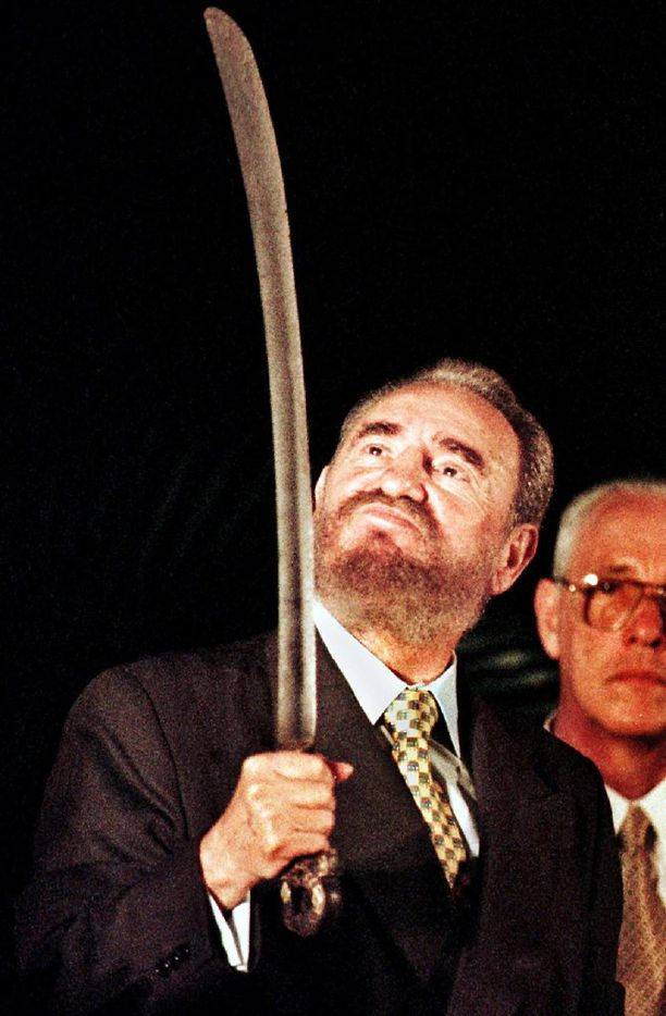 In this Aug. 24, 1998, file photo, Cuban President Fidel Castro (L) looks at a sword given to him by members of the Dominican Revolutionary Movement in Santo Domingo, on his last day of a three-day official visit to the Dominican Republic. The sword was originally used in the war of the Cuban independence against Spain.