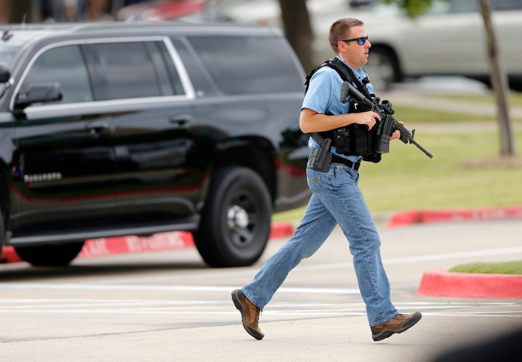 A policeman runs across the street after a shooting at North Lake College.