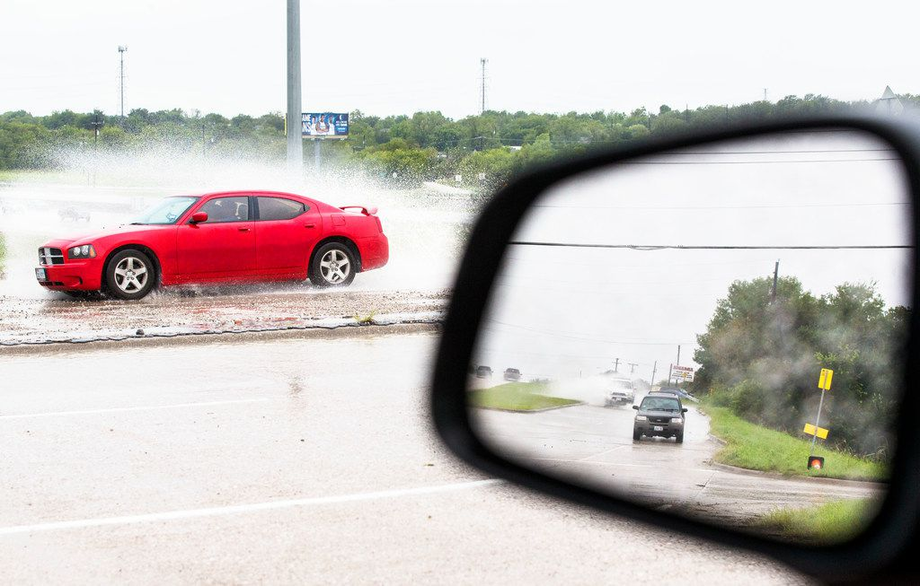 Cars drive through standing water at West Jefferson Boulevard and Loop 12 in Dallas on Oct. 13, 2018.  (Carly Geraci/The Dallas Morning News)