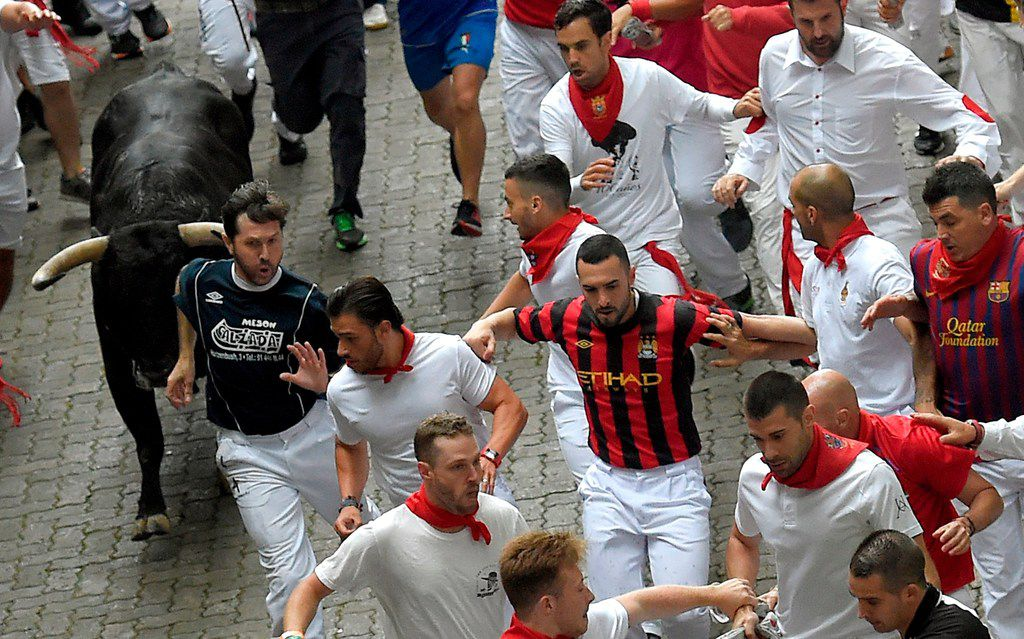 Participants run next to San Lorenzo 's fighting bulls on the first day of the San Fermin bull run festival in Pamplona, northern Spain.