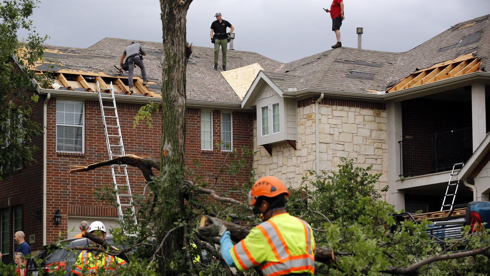 Oliver Drive in North Fort Worth was a hub of activity as crews covered damaged rooftops and disposed of splintered trees May 29.