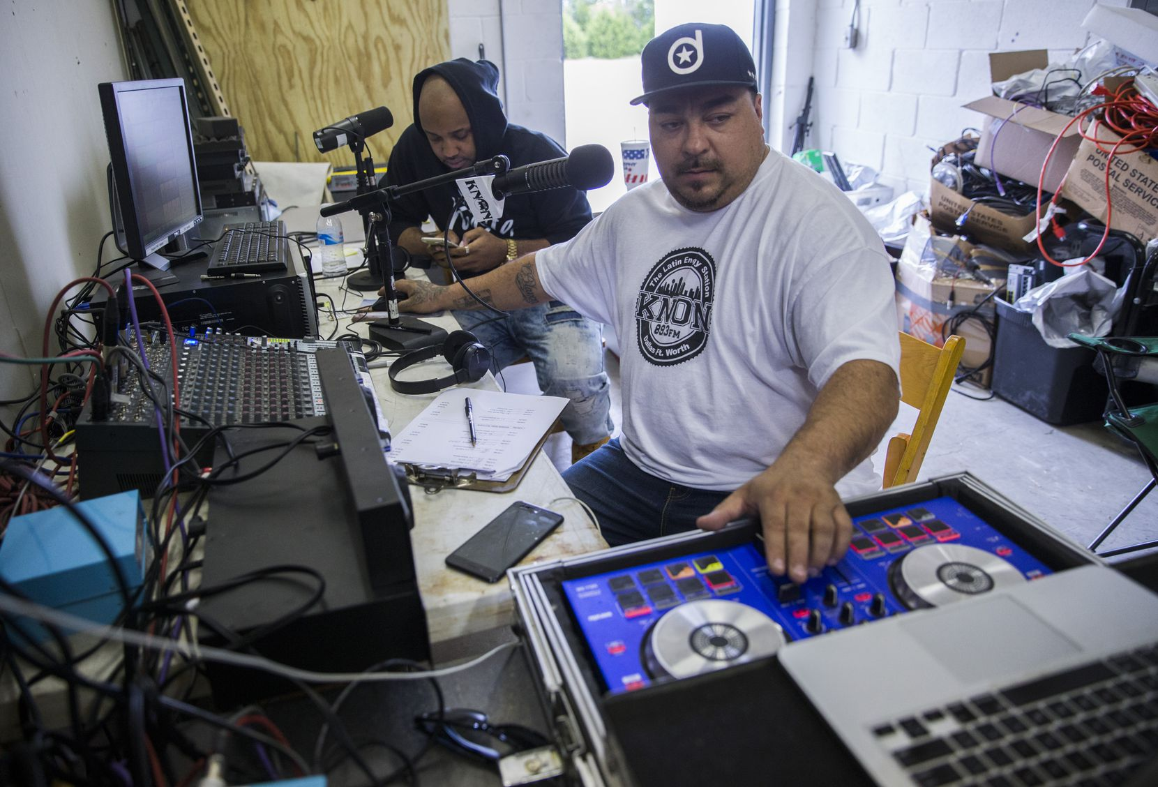 """KNON DJs Ruben """"Solo"""" Contreras (right) and Xavier Person, a.k.a. """"Romeo X,"""" host their radio show from a small storage building below the KNON radio antenna on Thursday, October 24, 2019 in Cedar Hill."""