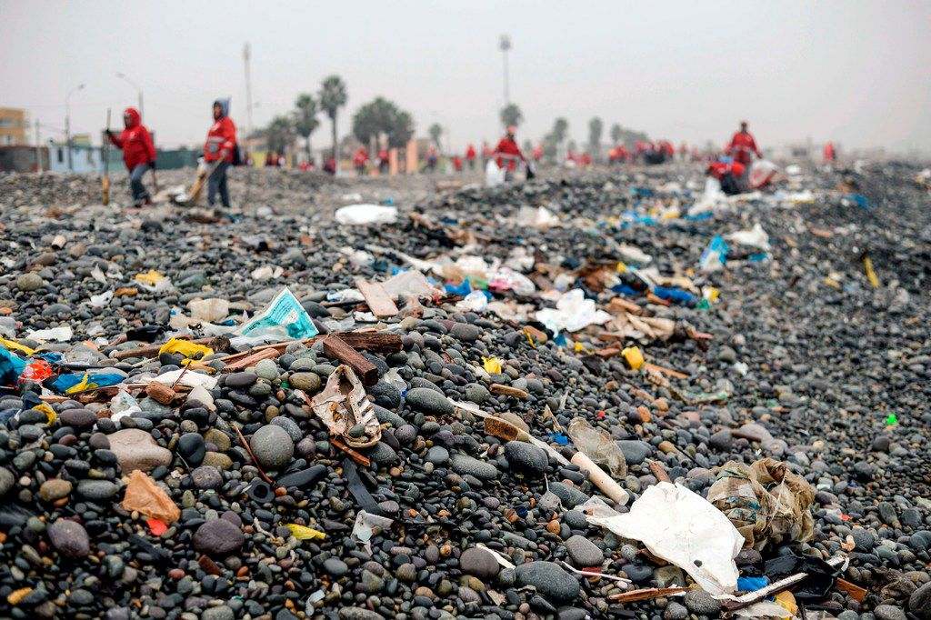 Groups of volunteers clean up plastic waste on a beach in Lima, Peru, during the World Environment Day on June 5, 2018. The UN urged to take steps against the use of plastic bags, as part of a global challenge to reduce the increasing pollution of the oceans.