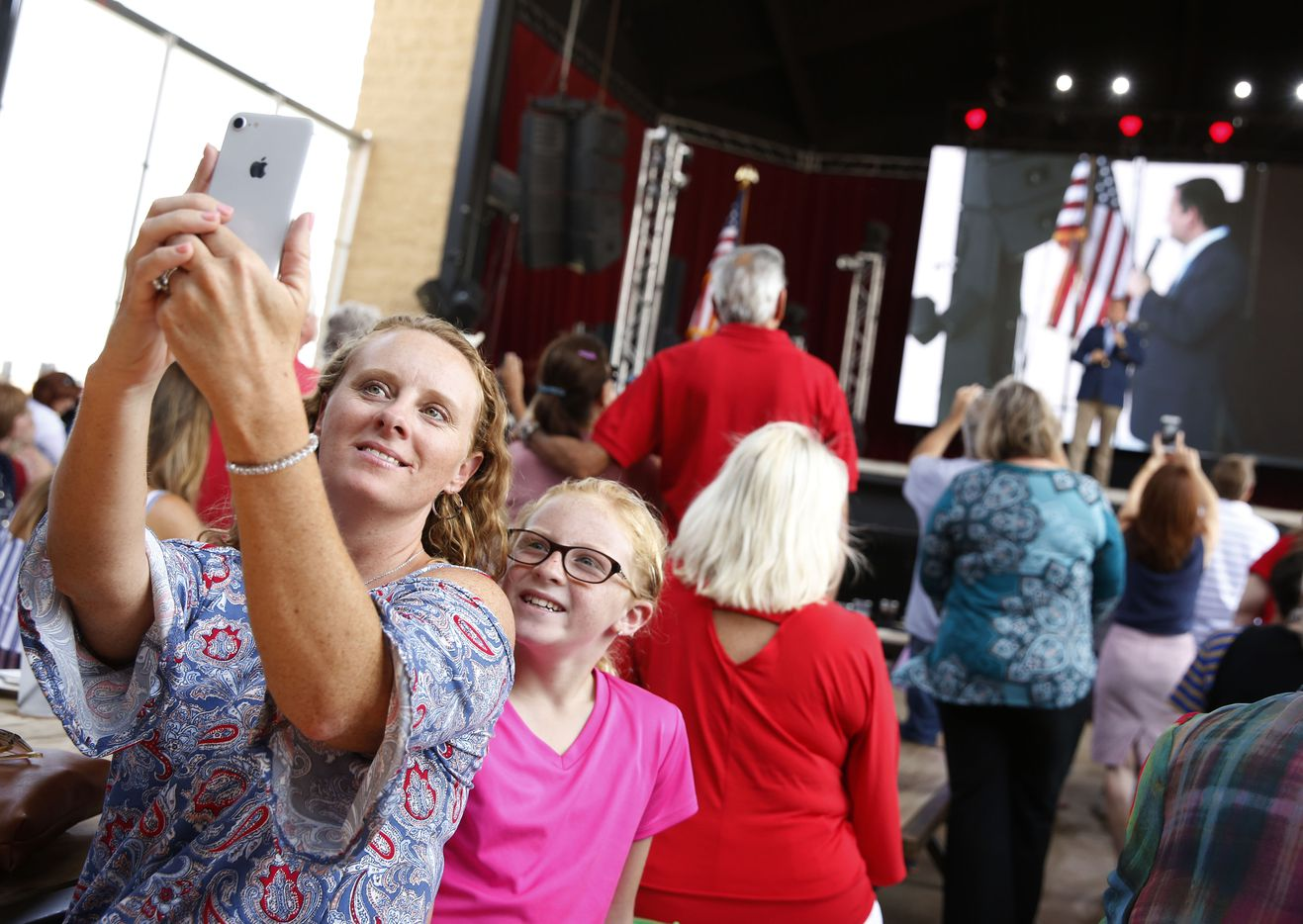 Jennifer Poshadlo takes a photo with her daughter Katelyn Poshadlo, 10, as Senator Ted Cruz gives a speech at Lava Cantina in The Colony, Texas on Aug. 27, 2018.