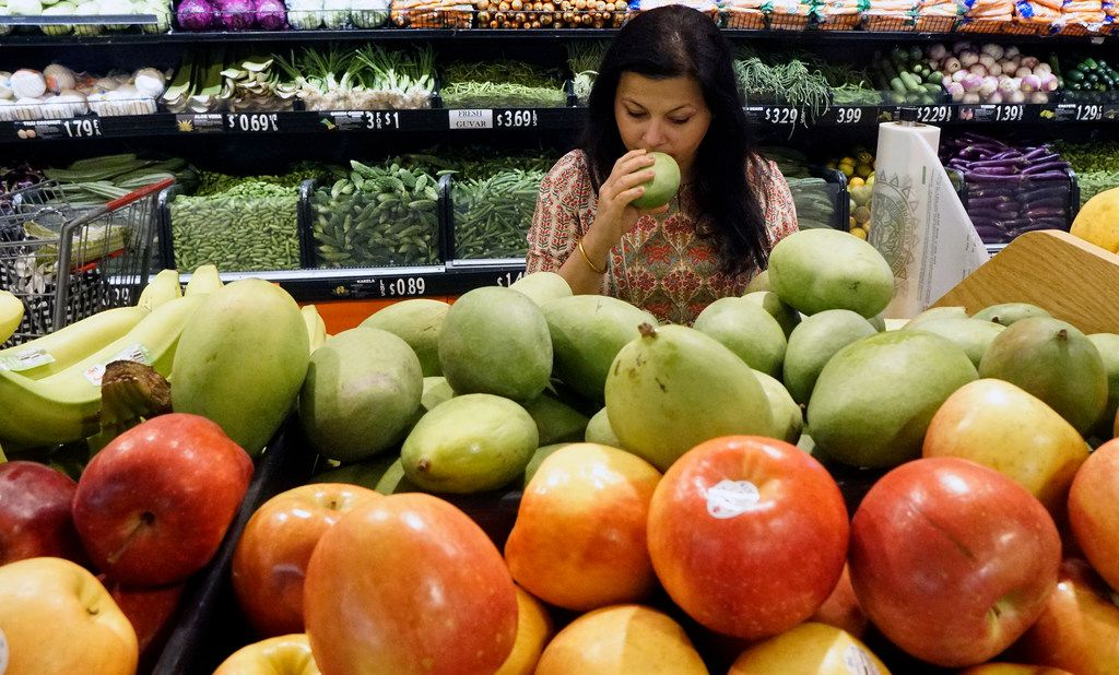 Sapna Punjabi-Gupta checks out the green raw mango at the India Bazaar in Irving, Texas on Tuesday, March 26, 2019.  (Lawrence Jenkins/Special Contributor)