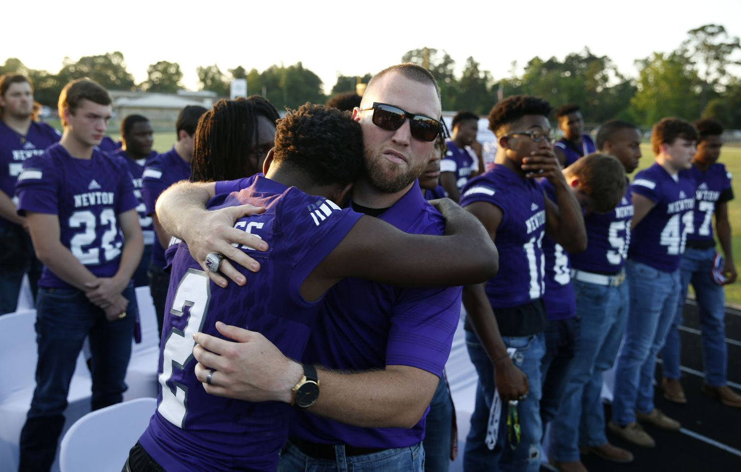 """Newton current head football coach and son Drew Johnston hugs Newton's Kevin Watson Jr. (2) during the memorial service for Newton High School head football coach William Theodore """"W.T."""" Johnston at Curtis Barbay Field at Newton High School in Newton, Texas on Wednesday, May 15, 2019. (Vernon Bryant/The Dallas Morning News)"""