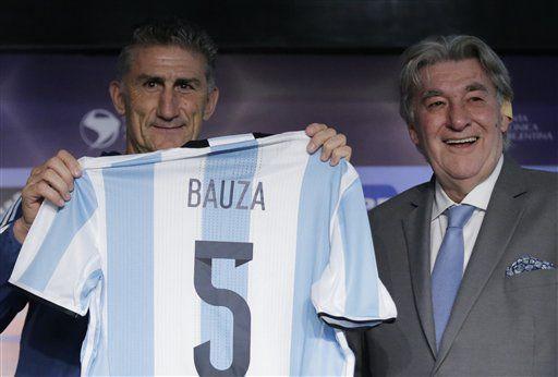 El nuevo entrenador de la selección de Argentina, Edgardo Bauza, recibe la camiseta oficial con su nombre y el número 5 por parte de Armando Pérez, presidente de la Asociación de Fútbol de Argentina, en Buenos Aires, el viernes 5 de agosto de 2016. (AP Foto/Jorge Saenz)