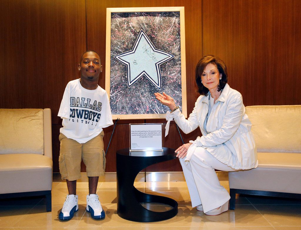 Gene Jones (right) poses for a photo with artist Kendrell Daniels who painted The Star, an acrylic painting for the Jones', in the owners suite at AT&T Stadium in Arlington, Texas, Sunday, September 8, 2019. The painting will be on display for the rest of the season.