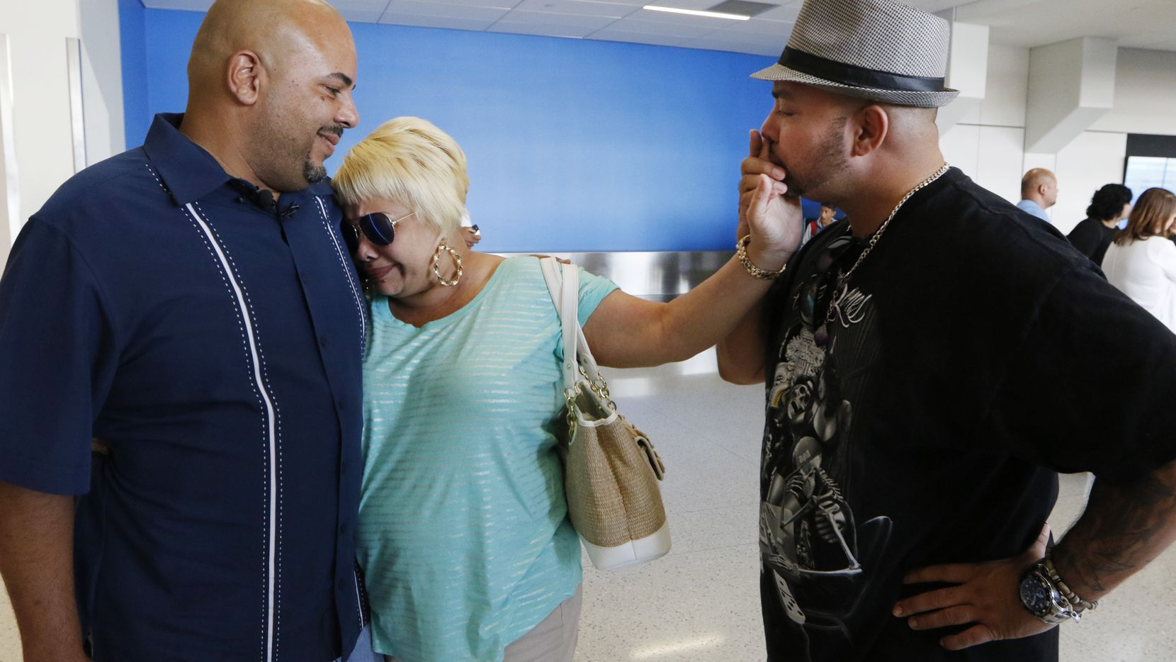 Anthony Wiggs (left) and Raymond Ramirez meet their biological mother, Elsie Ramirez, for the first time at DFW International Airport. The men were separated from their mother as infants, but a DNA search led them to her 47 years later.