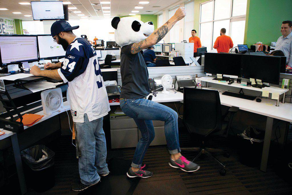 Wearing a panda head, Brandi Beakley dances near the desk of Cameron Ratcliff at Driversselect in Grand Prairie.