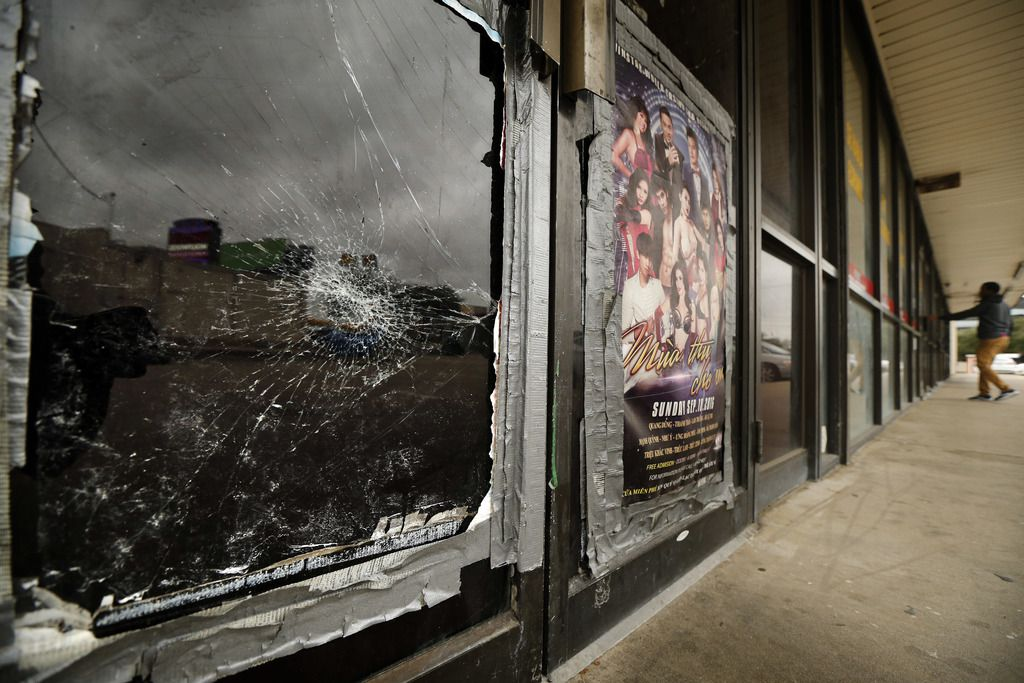 Broken glass and outdated casino posters are visible on the vacated storefront of 12125 Abrams Road, Suite 111.