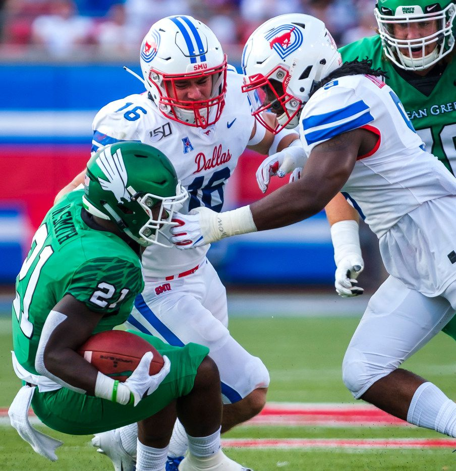 UNT running back Nic Smith (21) is brought down by the facemask by SMU linebacker Shaine Hailey (9) and safety Trevor Denbow (16) during the first half of an NCAA football game at Ford Stadium on Saturday, Sept. 7, 2019, in Dallas.