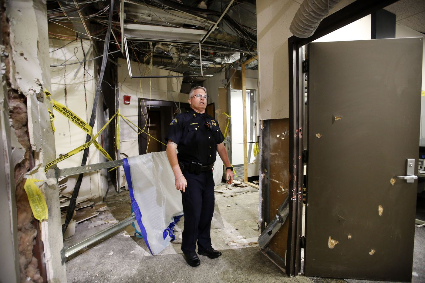 Dallas County College Police Chief Joseph Hannigan shows the spot where the gunman was cornered by police in a second-story hallway at El Centro College in downtown Dallas. The police detonated a bomb, killing the gunman and causing the structural damage.
