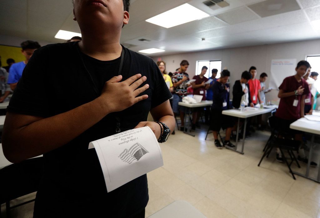 In this Tuesday, July 9, 2019, photo, immigrants say the Pledge of Allegiance in a writing class at the U.S. government's newest holding center for migrant children in Carrizo Springs, Texas. Following breakfast, children play soccer and then have classes held in trailers.