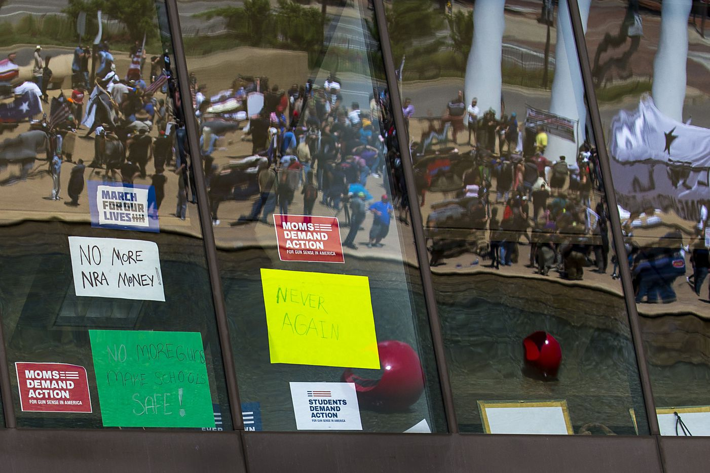 Gun rights advocates are reflected in Dallas City Hall, where a selection of gun control signs can be seen in the windows, as they demonstrate at a rally organized by Open Carry Texas during the NRA Annual Meeting & Exhibits at the Kay Bailey Hutchison Convention Center on Saturday, May 5, 2018, in Dallas. (Smiley N. Pool/The Dallas Morning News)