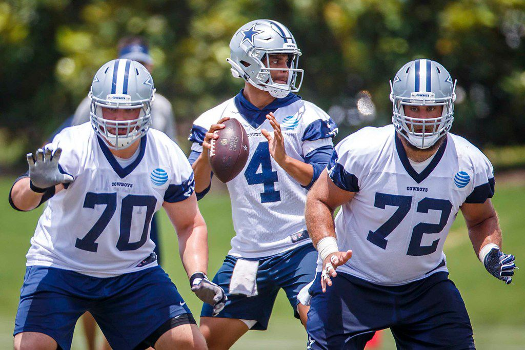 Dallas Cowboys quarterback Dak Prescott (4) throws a pass behind offensive guard Zack Martin (70) and center Travis Frederick (72) during the team's minicamp at The Star on Wednesday, June 13, 2018, in Frisco, Texas. (Smiley N. Pool/The Dallas Morning News)