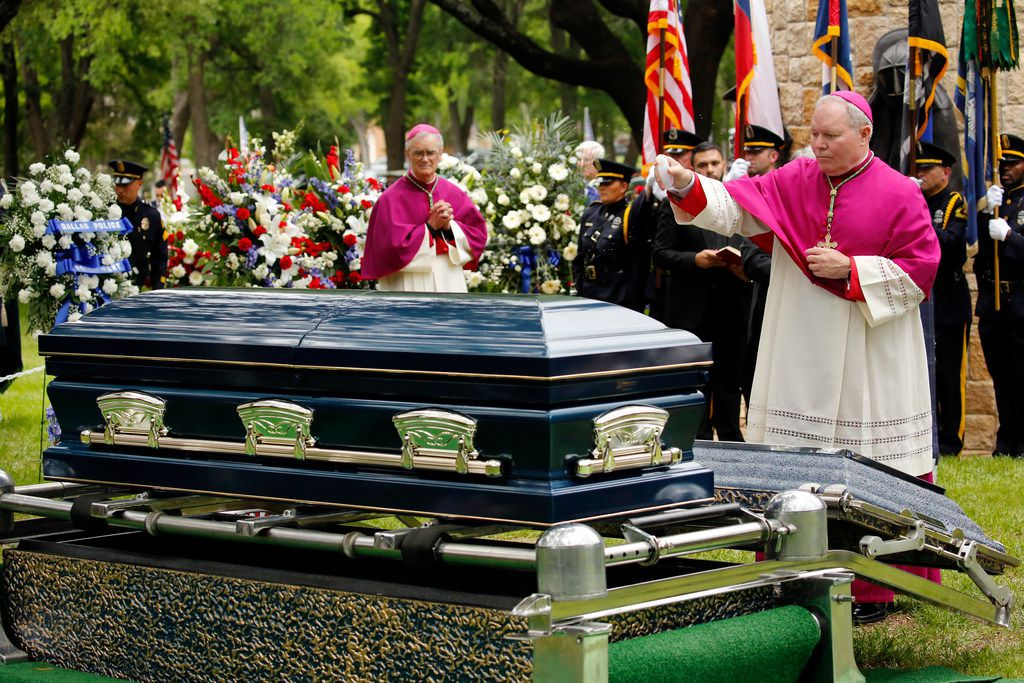 Dallas Bishop Edward J. Burns sprinkles the casket of Officer Rogelio Santander with holy water as he's laid to rest.