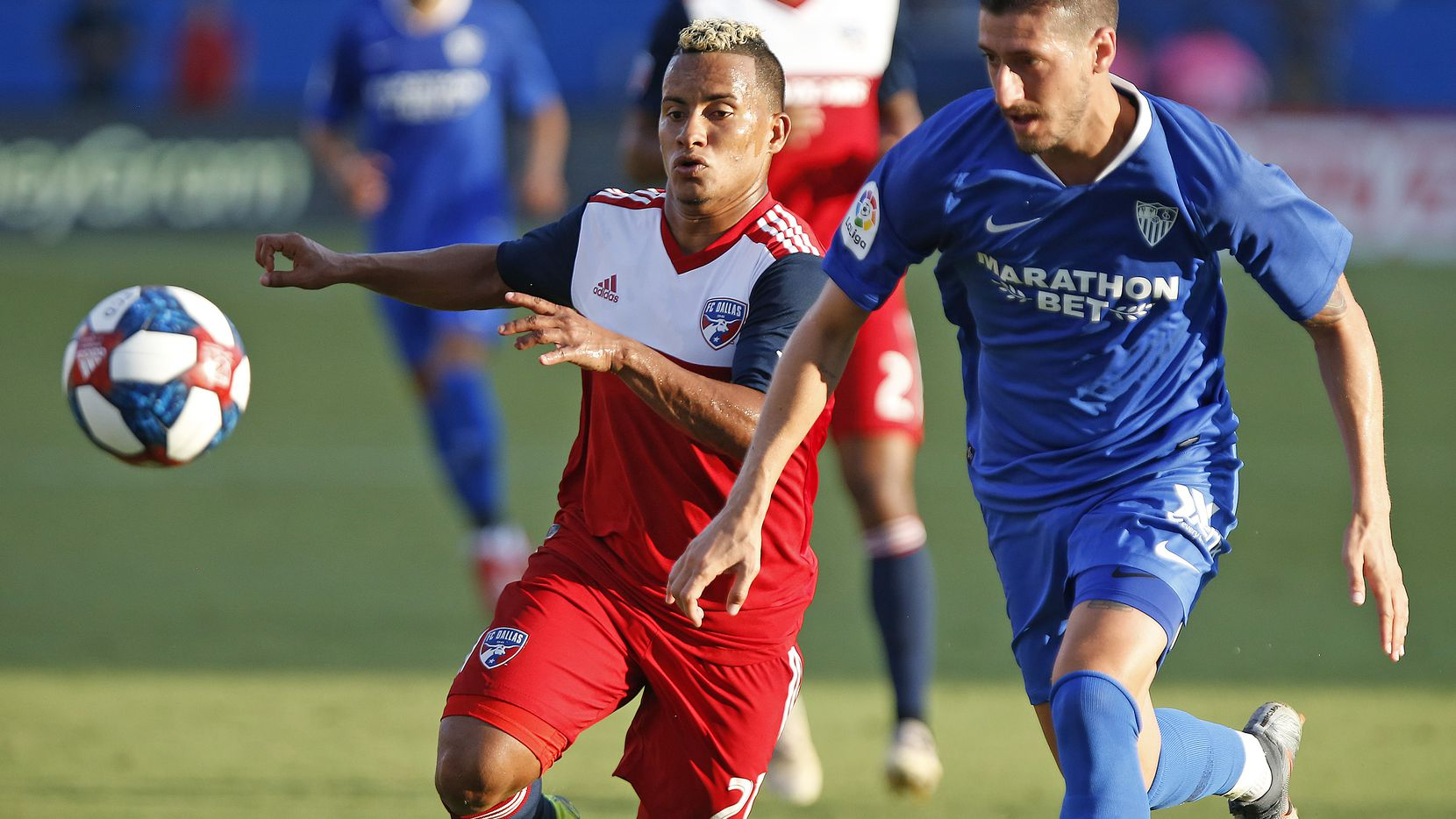 Michael Barrios (21) y Sergio Escudero (18) pelean por el balón en el amistoso entre FC Dallas y Sevilla el miércoles en el Toyota Stadium de Frisco.