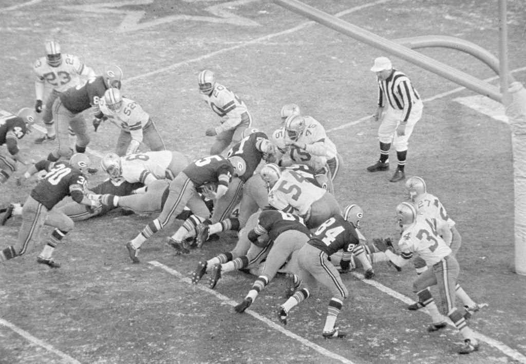 """FILE - In this Dec. 31, 1967, file photo, Green Bay Packers quarterback Bart Starr (15), follows his blockers including Jerry Kramer (64) against the Dallas Cowboys, including Jethru Pugh (75) for a touchdown, in the """"Ice Bowl,"""" in Green Bay, Wisc. Bart Starr died Sunday, May 26, 2019, in Birmingham, Ala. He was 85.  (AP Photo/Fikloe)"""