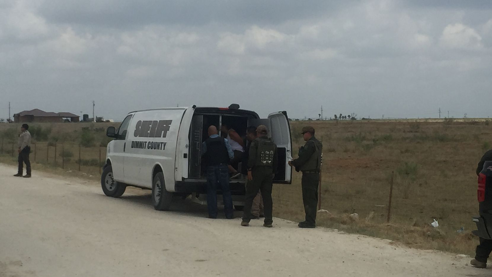 Dimmit County Sheriff's deputies inspect three people arrested following an immigration protest in Carrizo Springs where protesters called for an end to the detention of migrant children, following the opening of a new facility in the city.