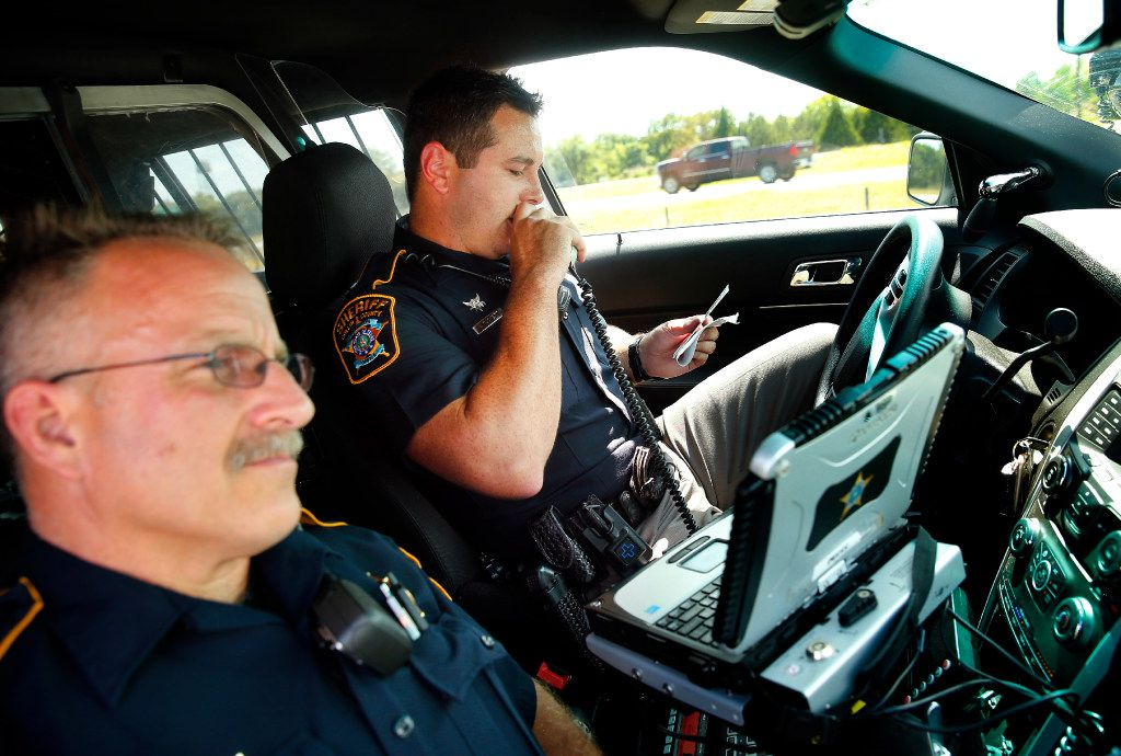 Collin County Sheriff's deputies Rodney Tackett (right) and Kelly Reynolds check a driver's license and registration during a traffic stop on U.S. Highway 75 in Collin County on Tuesday.