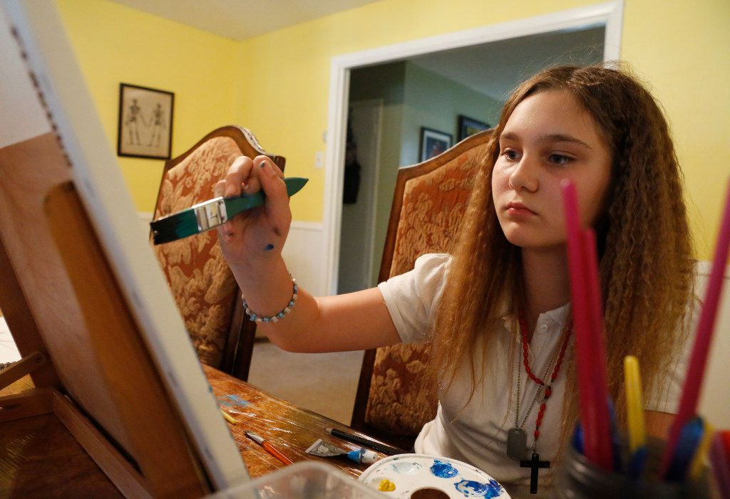 Alexis Brown concentrates on a painting in her Denison home. Art helps her focus and to better handle her medical issues, which include four heart surgeries.