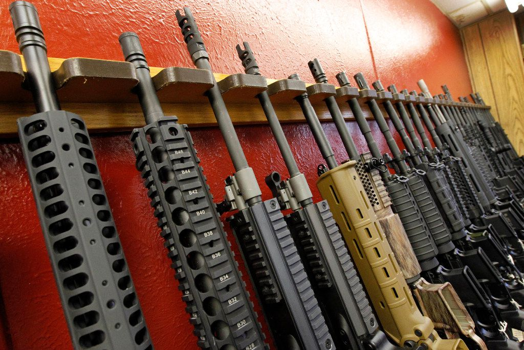 In this July 20, 2012, file photo, a row of different AR-15 style rifles are displayed for sale at the Firing-Line indoor range and gun shop in Aurora, Colo.