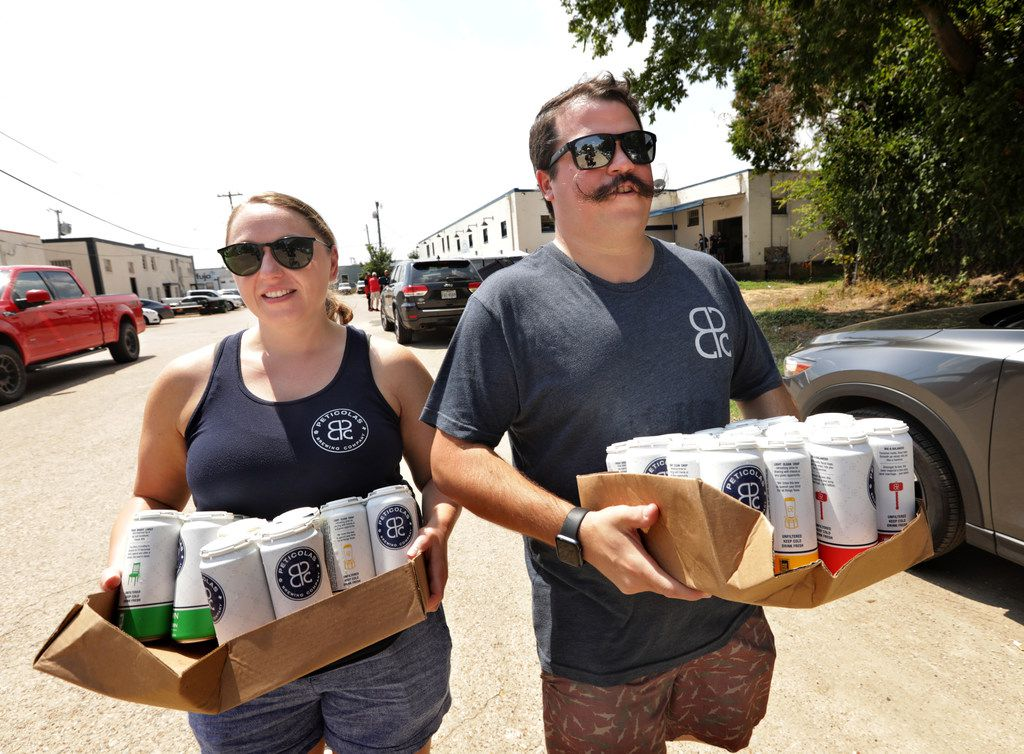Kenda Fanzo, left, and Dustin Fanzo carry beer to their car after purchasing it at Peticolas Brewing Company in Dallas, TX, on Sep. 1, 2019. Sunday, Sept. 1 is the first day Texans can purchase beer to go from breweries. Peticolas sold packaged beer for the first time after the Texas Legislature passed beer-to-go in May. The law allows customers to take home up to the equivalent of a case of beer.