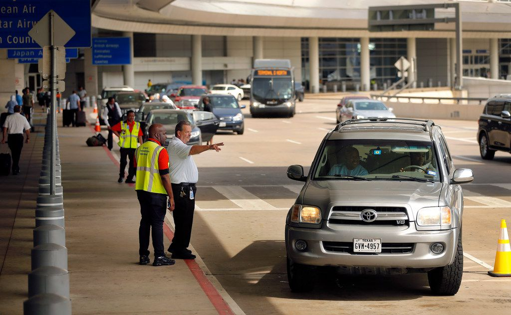 Terminal supervisor Peter Wuestenberg (pointing) directs a driver to move on from no stopping or standing location at DFW Airport's Terminal D, Wednesday, July 18, 2018. (Tom Fox/The Dallas Morning News)