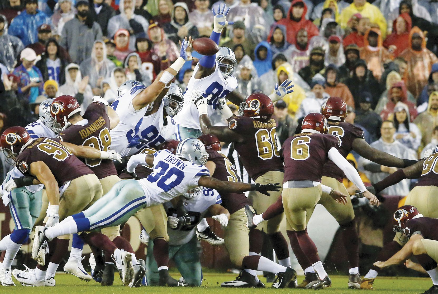 Dallas Cowboys defensive end Tyrone Crawford, with bandage on arm, blocks a field goal attempt by Washington Redskins kicker Nick Rose (6) during the second quarter at FedEx Field on Oct. 29.