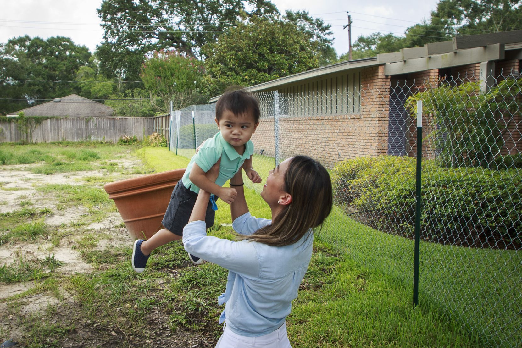 Cathy Pham plays with son Aidan at the site where their home once stood in southwest Houston. A year ago, a Dallas Morning News photo of their rescue went viral.