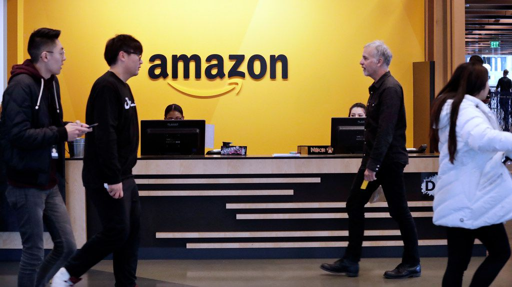 Employees walk through a lobby at Amazon's headquarters Nov. 13, 2018, in Seattle. Amazon, which is growing too big for its Seattle hometown, is spreading out to the East Coast. The online shopping giant ended its 14-month competition for a second headquarters Tuesday by selecting New York and Arlington, Va., as the joint winners.