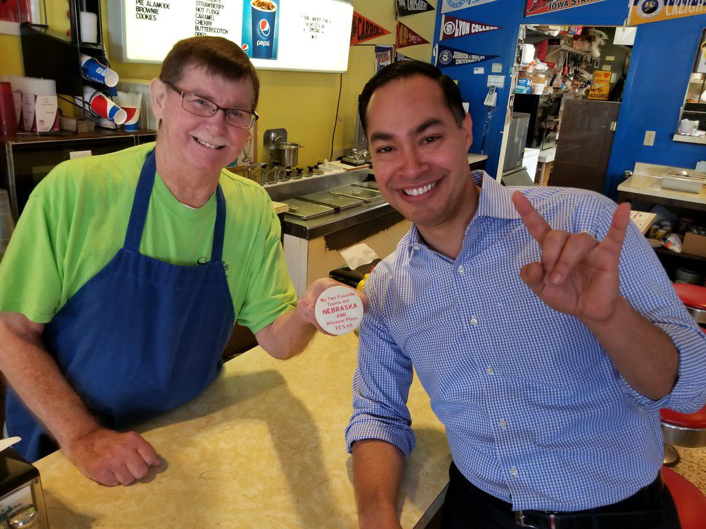 Julián Castro, stumping for president in Carroll, Iowa, poses with Sam Barta, owner of Sam's Sodas and Sandwiches, on Feb. 22, 2019.