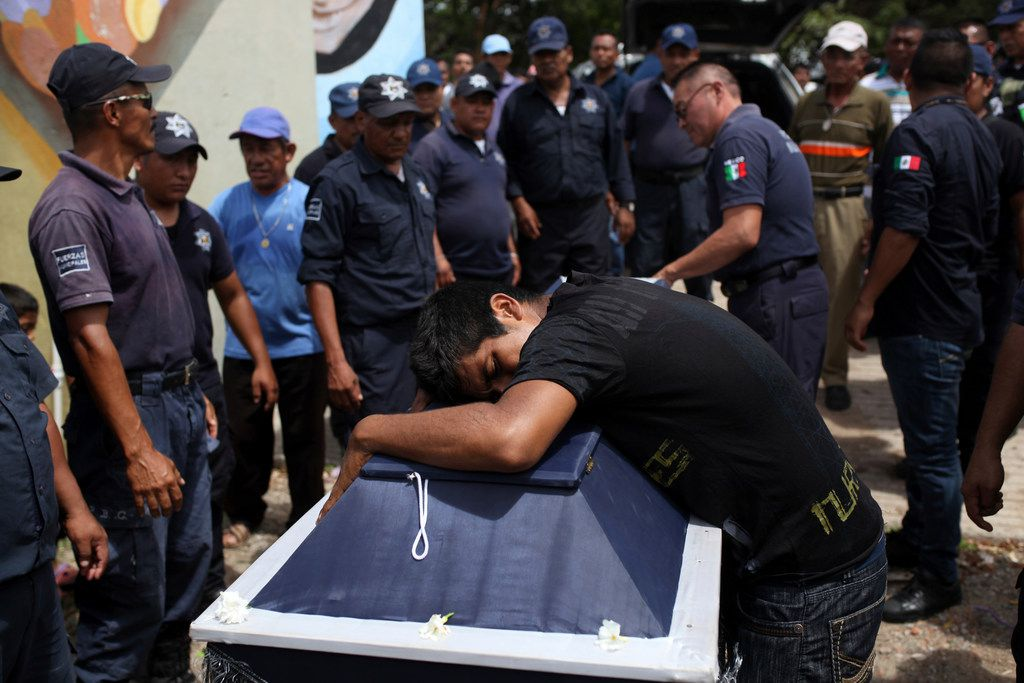 A man weeps on the coffin of Juan Jimenez Regalado, a police officer killed in Mexico's 8.1-magnitude earthquake Sept. 8, during his funeral in Juchitan, Oaxaca state, Mexico.