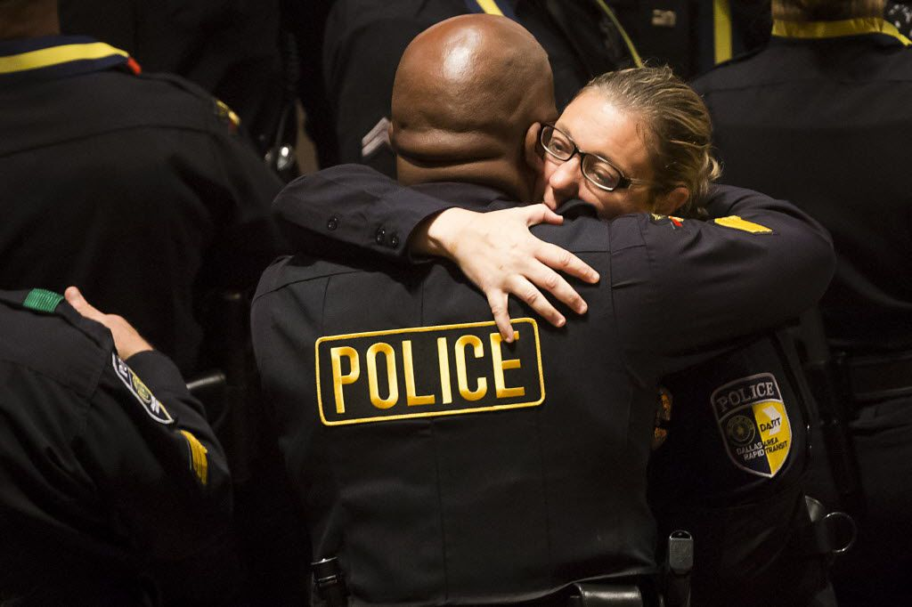 Injured Dallas Area Rapid Transit police officer Misty McBride gets a hug as she arrives for interfaith memorial service at the Morton H. Meyerson Symphony Center on July 12 for five law enforcement officers killed this month in an ambush at a Black Lives Matter rally.